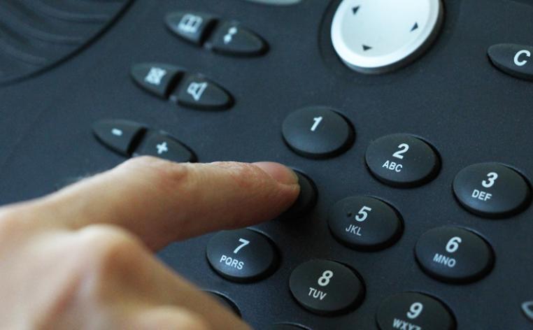 Photo d'une personne appuyant les touches d'un clavier téléphonique