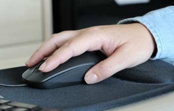 Main sur une souris d'ordinateur